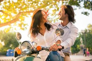 fröhliches europäisches Paar, das auf Roller flirtet