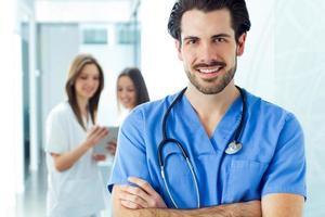 fröhlicher junger Arzt, der sein Team führt foto