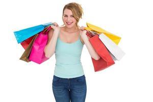 fröhliche blonde Frau, die Einkaufstaschen hält foto