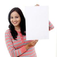 fröhliche junge Frau, die leere weiße Tafel hält foto