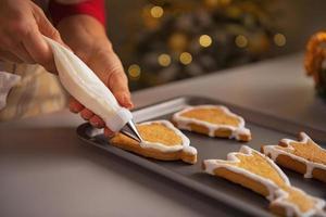 Nahaufnahme auf Hausfrau, die Weihnachtsplätzchen mit Glasur verziert foto