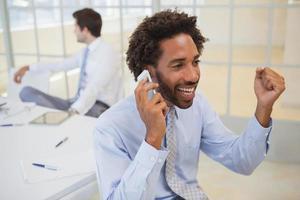 fröhlicher Geschäftsmann, der Handy im Büro benutzt foto