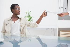 fröhliche Frau, die Papier von ihrem Kollegen nimmt foto