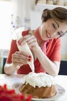 Frau, die einen Kuchen in der Küche vereist foto
