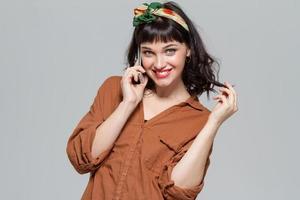 schöne fröhliche junge Frau, die auf Handy spricht foto