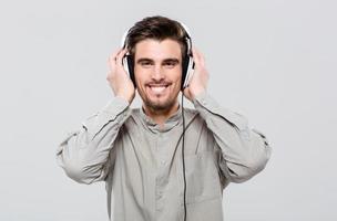 glücklicher fröhlicher junger Mann, der Musik hört foto