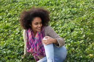 fröhliche junge Frau, die draußen auf Gras sitzt foto