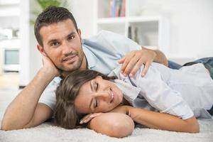 fröhliches junges Paar, das auf Teppichboden liegt