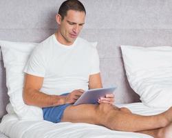 fröhlicher Mann mit Tablet-PC auf dem Bett foto