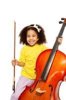 fröhliches afrikanisches Mädchen hält Cello mit Fiddlestick foto