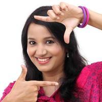 fröhliche junge Frau, die einen Rahmen mit den Fingern schafft foto