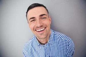 Porträt eines fröhlichen Mannes, der Kamera betrachtet foto
