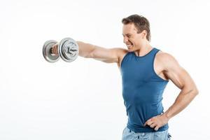 fröhlicher junger Sportler trainiert mit Eisenausrüstung foto