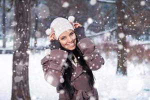 fröhliche Frau, die im verschneiten Park herumspielt
