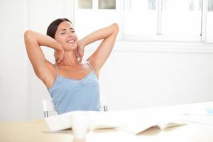 fröhliche erwachsene Frau, die entspannt sitzt und schaut foto