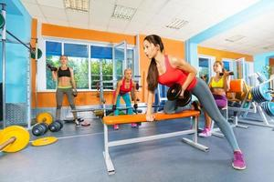 Mädchen im Fitnessclub heben Hanteln foto