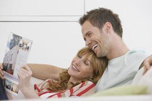 fröhliches Paar, das auf der Couch liest, die Zeitschrift liest foto
