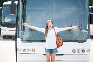 fröhliche junge Frau posiert in der Nähe von öffentlichen Verkehrsmitteln foto