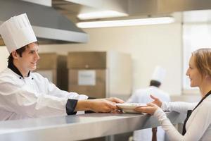 Koch gibt der Kellnerin einen Teller foto