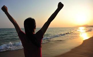jubelnde Frau offene Arme zum Sonnenuntergang am Meer