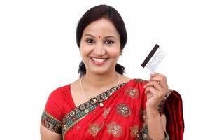 fröhliche traditionelle indische Frau, die eine Kreditkarte hält