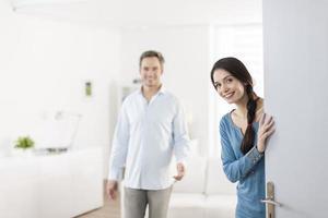 fröhliches Paar, das Leute einlädt, nach Hause einzutreten foto