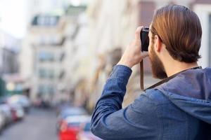 Der fröhliche bärtige Fotograf macht Fotos von der Stadt