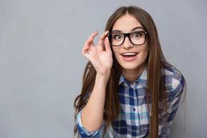 neugierige fröhliche Frau in den Gläsern, die Kamera betrachten foto