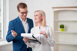 fröhlicher Immobilienmakler spricht mit einem Kunden foto