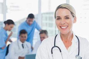 fröhlicher blonder Doktor, der mit Kollegen im Hintergrund aufwirft foto