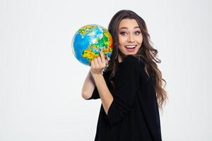 fröhliche Frau, die Globus hält und Kamera betrachtet