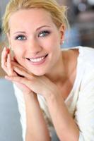 Nahaufnahme der fröhlichen blonden Frau mit den blauen Augen foto