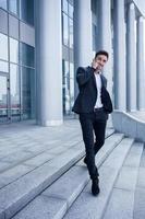 fröhlicher junger Geschäftsmann telefoniert foto