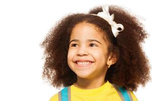 fröhliches afrikanisches Mädchen, das weißen Bogen im Haar trägt