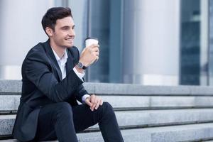 fröhlicher Mann im Anzug entspannt sich mit heißem Getränk foto