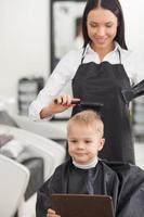 Der fröhliche junge Friseur benutzt einen Trockner im Friseursalon foto