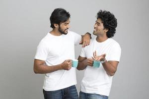 glückliche fröhliche junge Leute, die mit Tasse Tasse plaudern foto