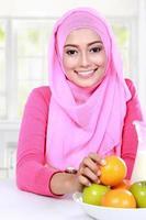 fröhliche junge muslimische Frau hatte Früchte zum Frühstück foto