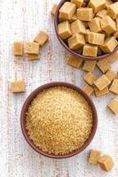 eine Schüssel brauner Zucker mit Zuckerwürfeln auf der Seite foto