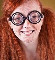 fröhliches sommersprossiges nerdiges Mädchen