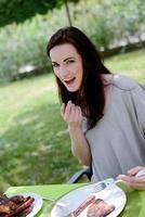 fröhliche junge Frau havign Mittagessen an der Grillparty im Freien