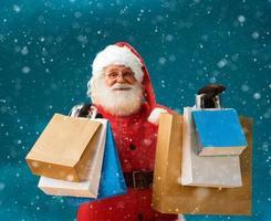 fröhlicher Weihnachtsmann draußen im Schneefall, der Einkaufstaschen hält foto