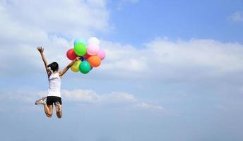 jubelnde Frau, die mit bunten Luftballons zum blauen Himmel springt foto