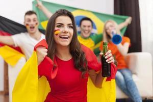 schönes spanisches Mädchen mit ihren Freunden jubeln Fußballspiel