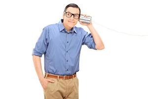 fröhlicher junger Mann, der durch ein Blechdosentelefon spricht