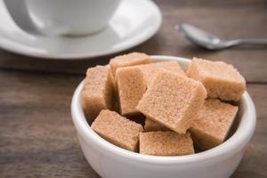 braune Zuckerwürfel in Schüssel und Kaffeetasse