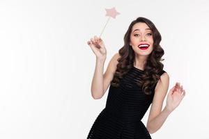fröhliche schöne lockige junge Frau, die mit Zauberstab aufwirft foto