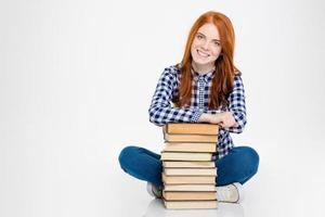 fröhliche Dame, die sitzt und sich auf Stapel Bücher stützt foto