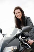 fröhliche und schöne junge Frau, die ein schwarzes Motorrad fährt