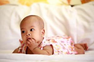 asiatisches Baby, das ihren Daumen saugt foto